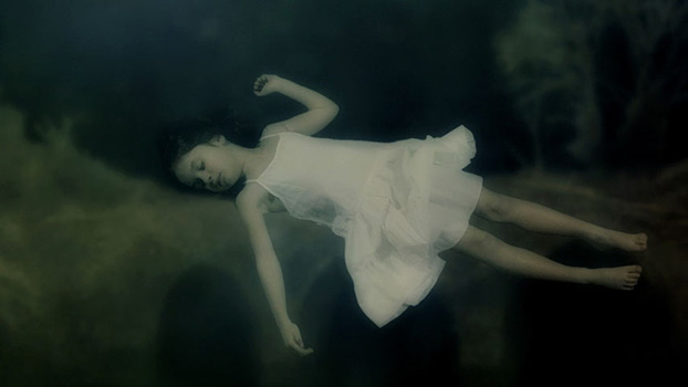 A child with a white dress sleeping underwater