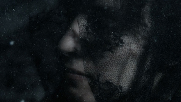 A woman with a black veil underwater