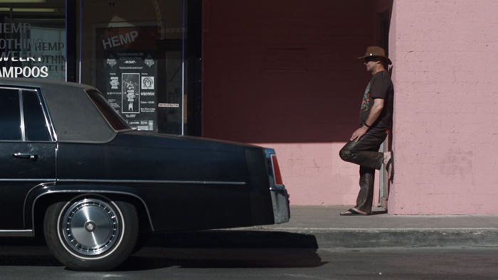 A man wearing a cowboy hat rest agains a pink wall next to a black car