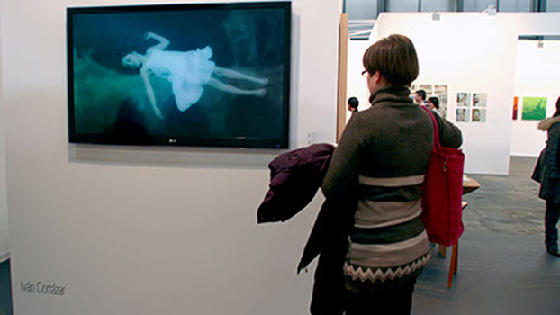 A woman at the ARCO art fair stares at a TV displaying an image of a child sleeping underwater