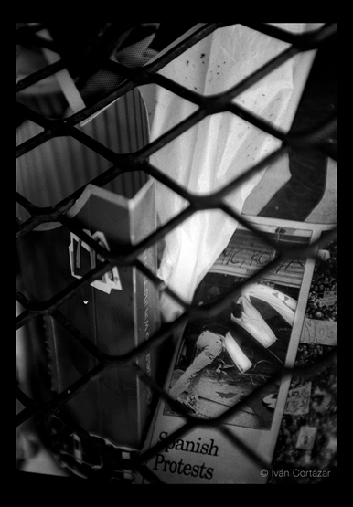 A black and white photo of a newspaper with Iraqi war headlines and imagery mixed with a Mac Donald's friends container inside a wired trash can.