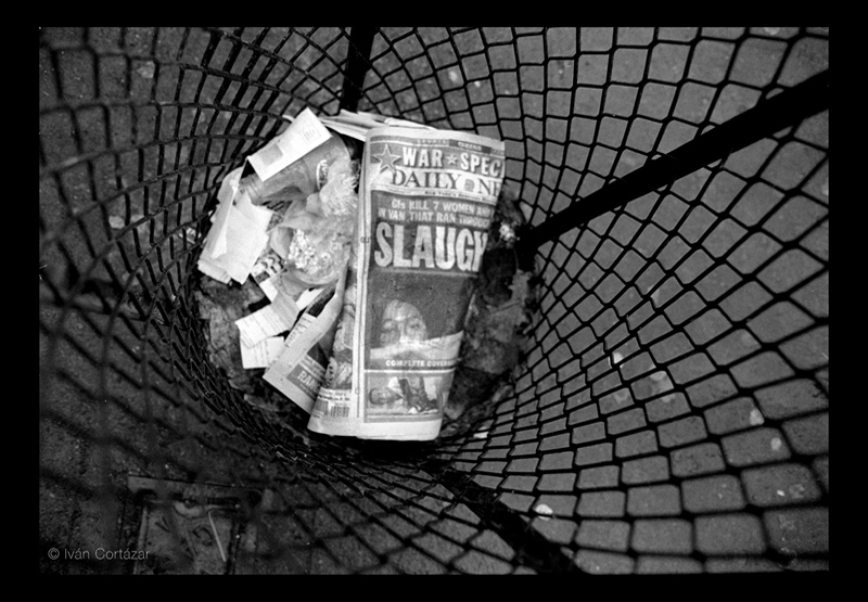 A black and white photo of a newspaper with Iraqi war headlines and imagery inside a wired trash can.