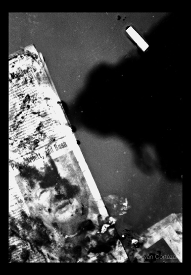 A black and white photo of a newspaper with Iraqi war headlines and imagery on a puddle of water