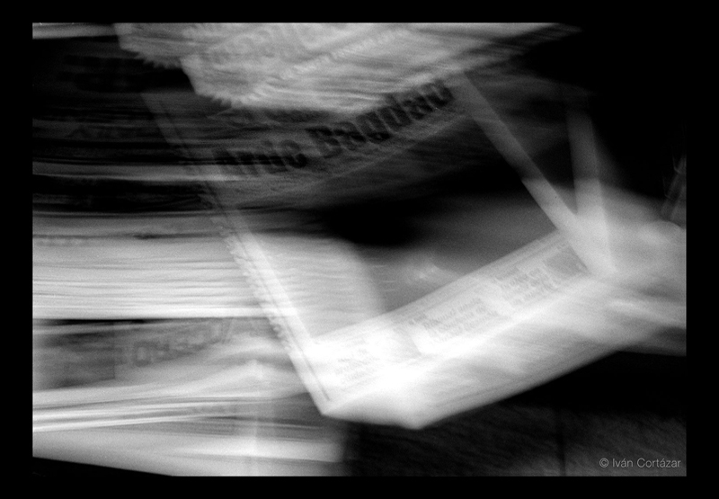 A blurry black and white photo of a newspaper with Iraqi war headlines in Spanish