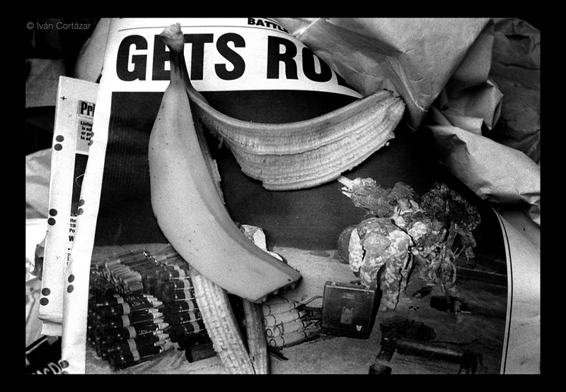 A black and white photo of a newspaper with Iraqi war headlines and imagery with a banana pill on top of it.