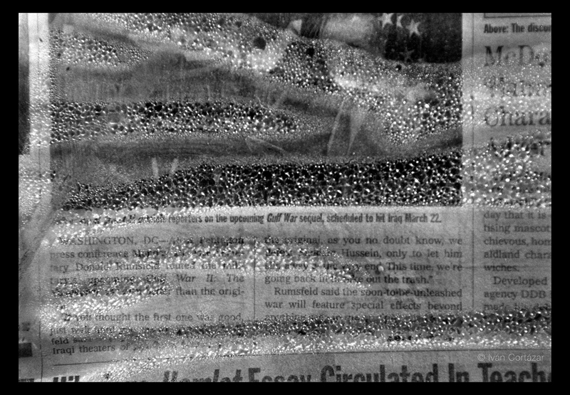 A black and white photo of a newspaper with Iraqi war headlines and imagery inside a plastic wrap covered with bubbles