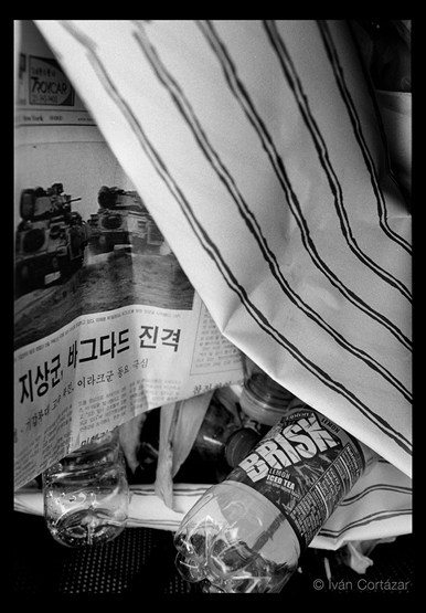 A black and white photo of a newspaper with Iraqi war korean headlines and imagery inside a wired trash can.
