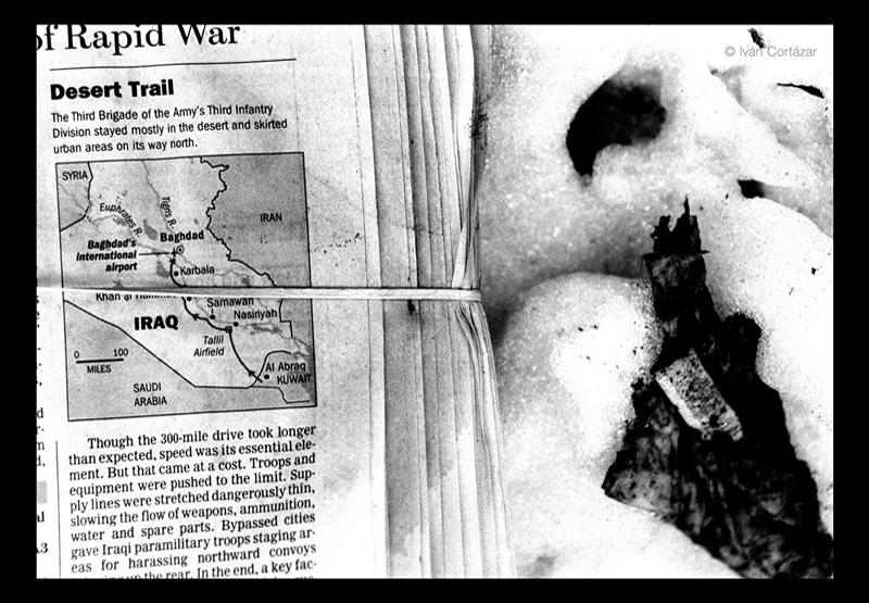 A black and white photo of a newspaper with Iraqi war headlines on the trash