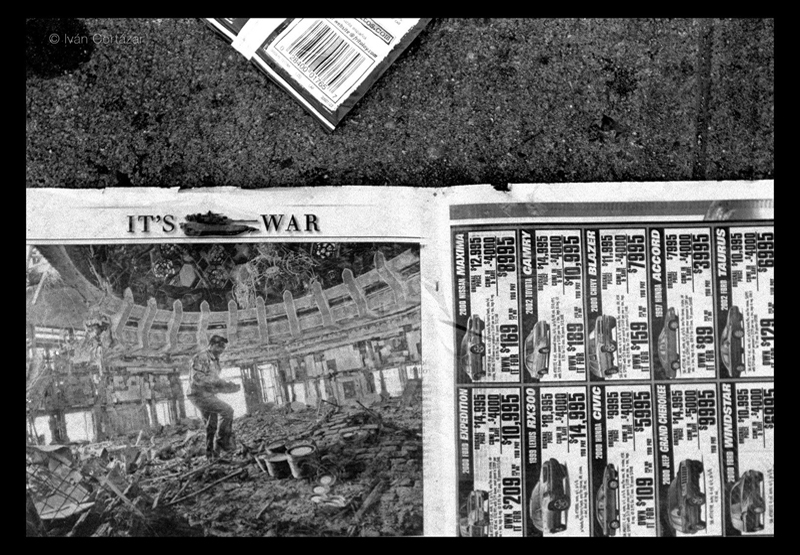 A black and white photo of a newspaper with Iraqi war headlines and imagery on the pavement.