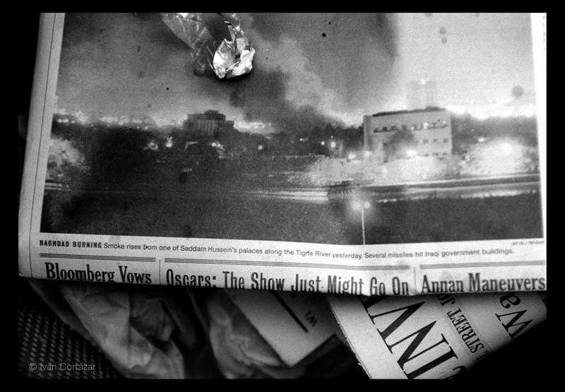 A black and white photo of a newspaper with Iraqi war headlines and imagery in a trash can